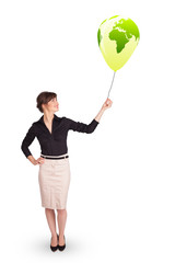 Happy lady holding a green globe balloon