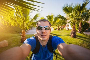 man is making selfie in the palm garden
