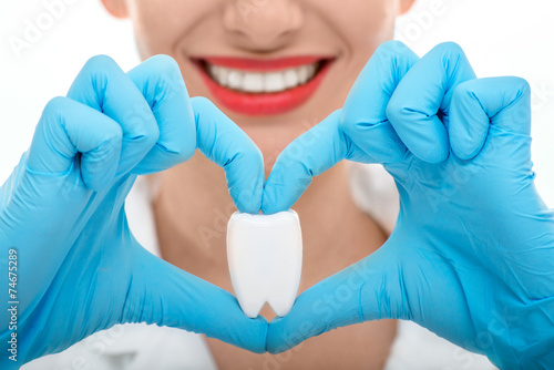 Portrait of dentist with tooth on white background - 74675289