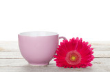 Cup of coffee and gerbera on wooden table
