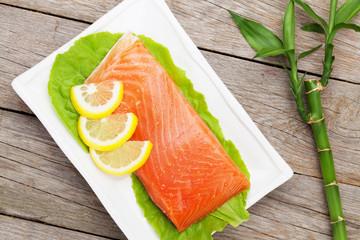 Fresh salmon fish with lemon and salad leaves