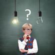Schulkind vor Tafel mit Fragezeichen / Lampen