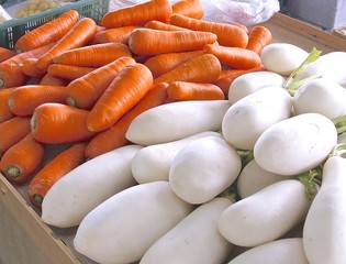 The close view of fresh white radish and carrots