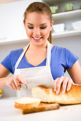 Smiling girl in kitchen cutting bread