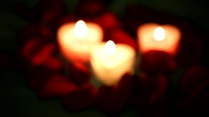 Rose petals and a burning candle.Variable focus