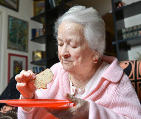 Old woman eating a slice of  bread