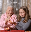 Girl giving mandarin oranges to his grandmother