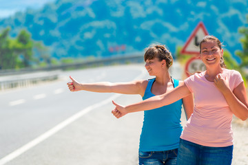 funny young girl hitchhiking in the mountains