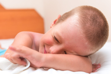5 years old boy pretending to be asleep