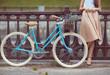 Leinwandbild Motiv Young beautiful, elegantly dressed woman with bicycle