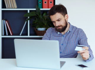 Young bearded man pays by credit card online shopping