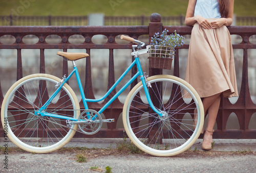 Young beautiful, elegantly dressed woman with bicycle poster