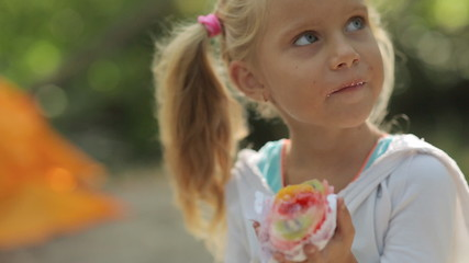 Amazing little girl with blue eyes eating cake with fruit on the