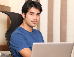 Young Indian business man in casuals with a laptop