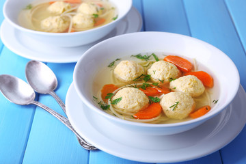 Soup with meatballs and noodles in bowls
