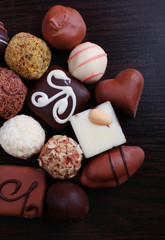 Assorted chocolates on the dark wooden smooth background