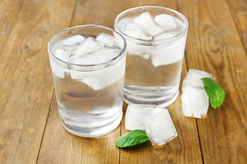 Glass of water with ice cubes on wooden table