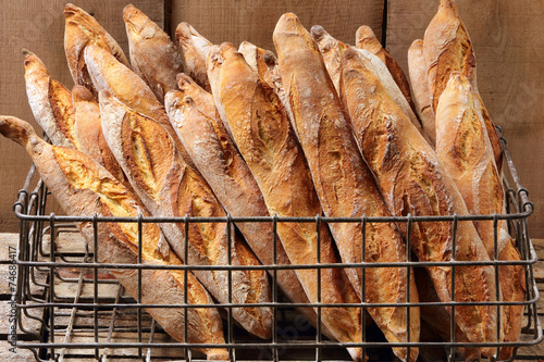 Foto op Canvas Bakkerij French baguettes in metal basket in bakery