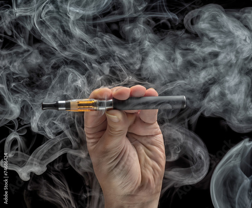 Hand holding an electronic cigarette over a dark background - 74686424