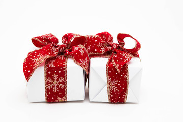 Two cute gift boxes with red ribbons isolated on white