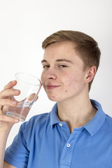 portrait of attractive caucasian teenage boy drinking water