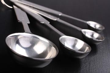 Empty metal measuring spoons on black background