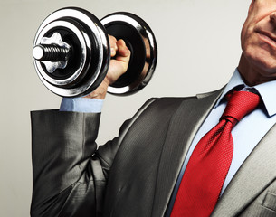 Image of businessman in suit raising dumbbell. Tax burden concep