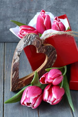 Beautiful pink tulips with gift box and wooden heart