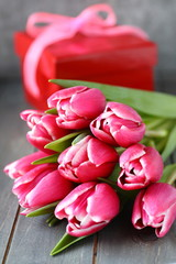 Beautiful pink tulips with gift box on wooden background