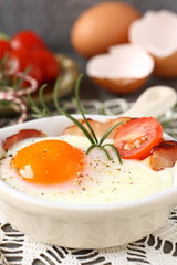 Fried egg with bacon in ceramic pan on wooden background
