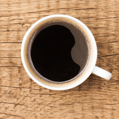 Coffee cup on wooden table - view from top