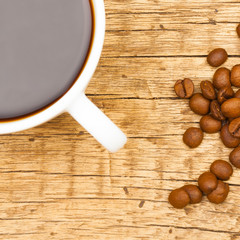 Close up of neat coffee cup with roasted coffee beans