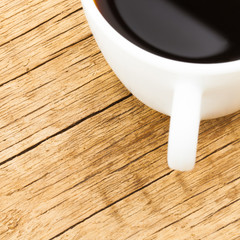 Close up of white ceramic coffee cup on old wooden table