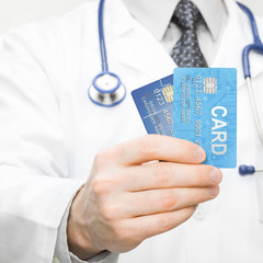 Doctor holding two credit cards in his hand