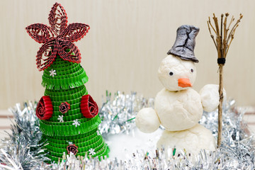 Snowman with broom in hand near Christmas tree