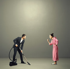 man in suit holding vacuum cleaner