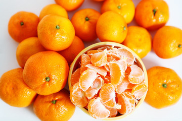 fresh tangerines peeled in ceramic bowl