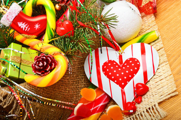Pine twigs, heart, christmas balls, cones on sacking background