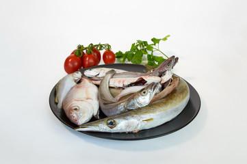 Fish assorted Mediterranean platter on black plate.