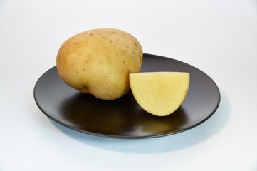 Large potatoes and half on plate closeup