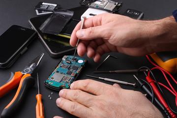 Tecnico al lavoro nel riparare cellulari guasti