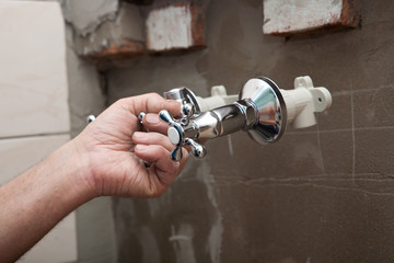 plumber at work install faucets