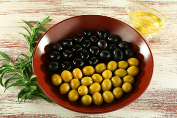 Black and green olives in bowl with branch