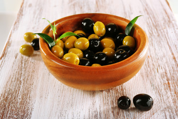 Black and green olives with leaves in bowl