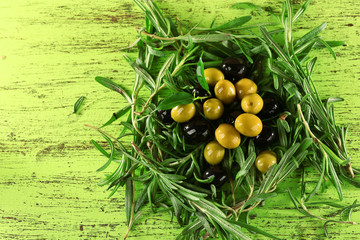 Pile of branches and olives on painted wooden background