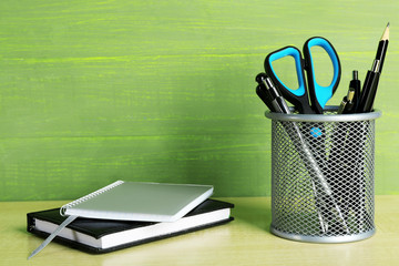 Metal holder with pens, pencil and scissor near the notebooks