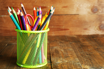 Colorful pencils with scissors in metal holder