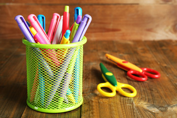 Metal holder with different pens and scissors