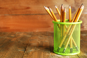 Pencils in metal holder on rustic wooden background