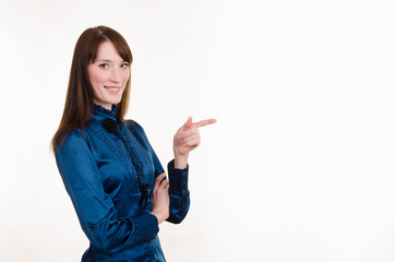 Young girl in a blue blouse pointing at empty space on left